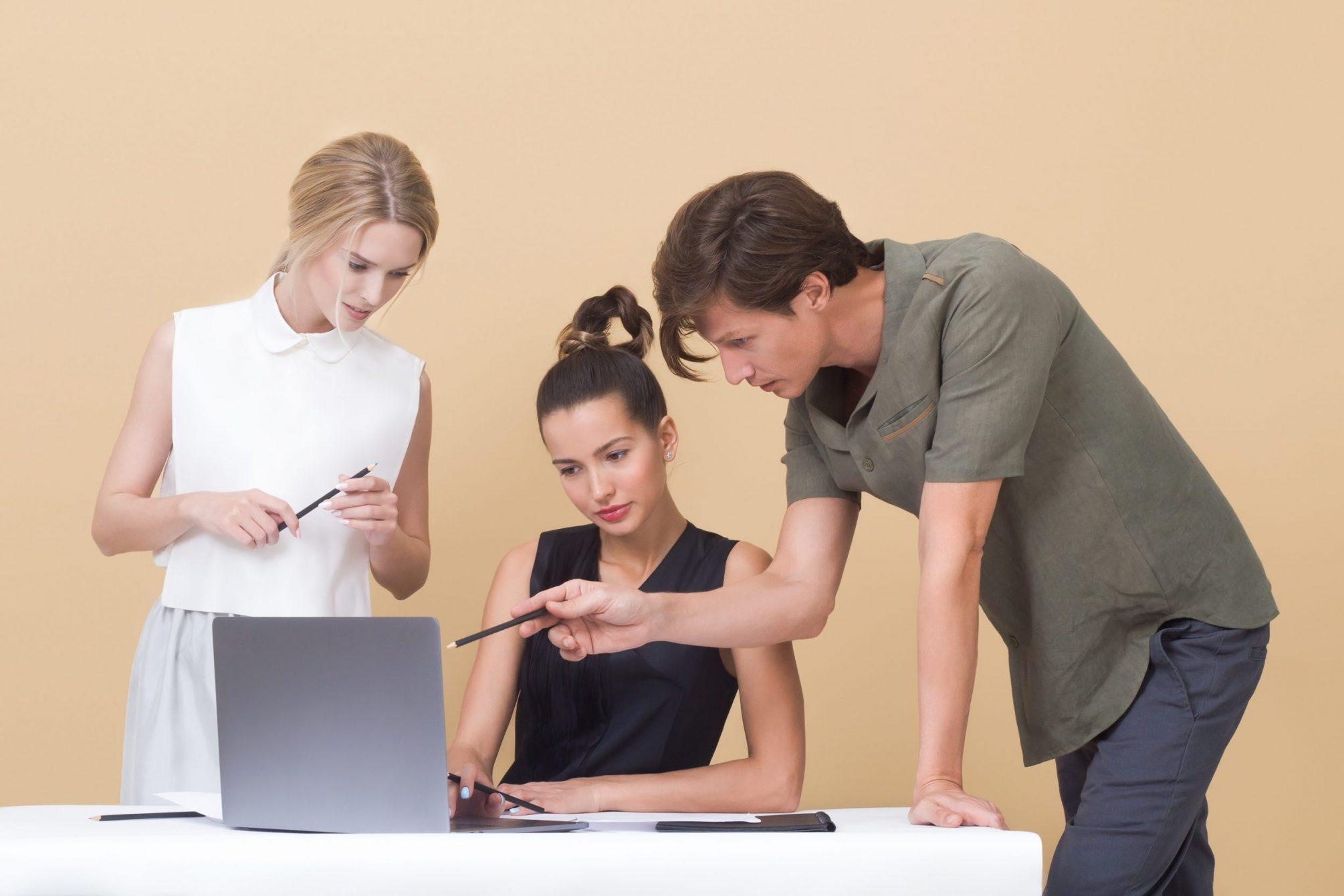 Dua orang remaja wanita dan satu remaja pria sedang menunjuk ke laptop berwarna abu-abu sedang berdiskusi tentang kebiasaan finansial