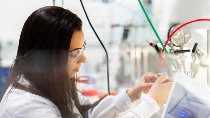 Seorang insinyur wanita sedang bekerja di dalam laboraturium.