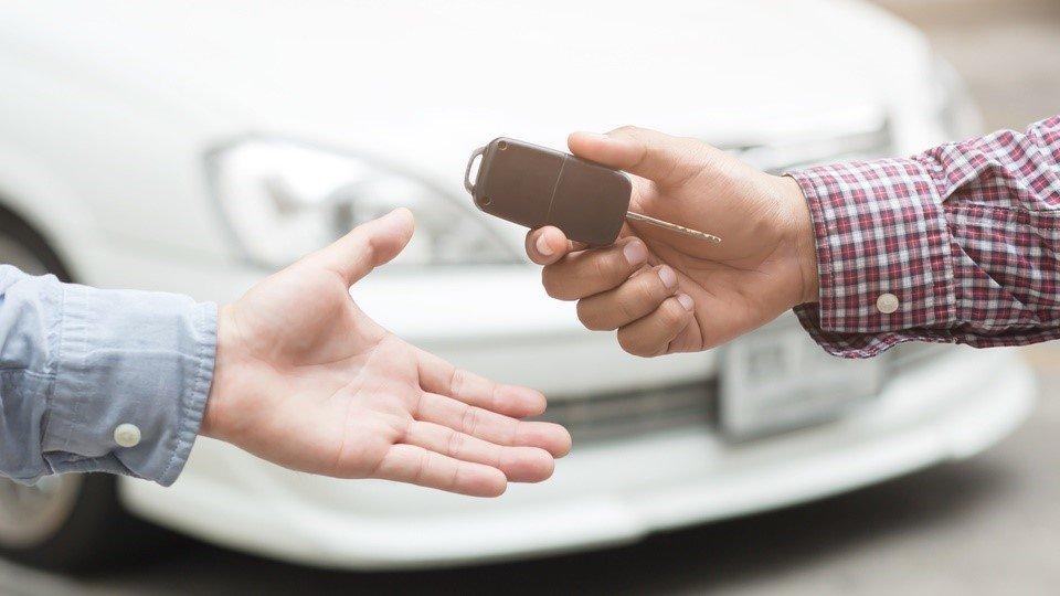 seorang pria menyerahkan kunci mobil pada pria lainnya