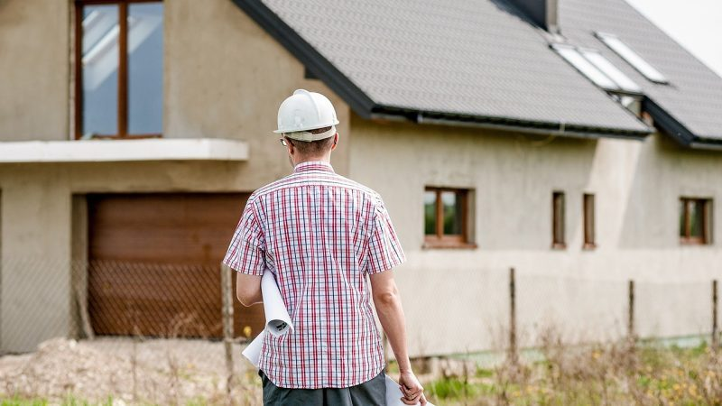 Seorang kontraktor sedang menatap bangunan rumah.