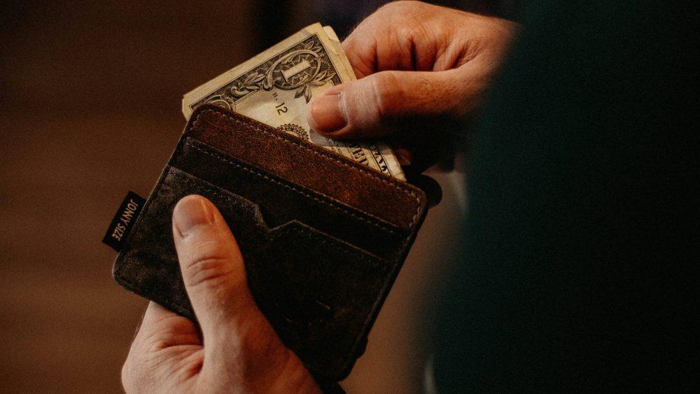 Seseorang sedang mengeluarkan uang dari dompetnya.