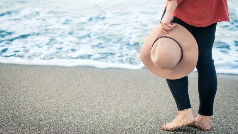 Seseorang sedang berdiri di tepi pantai sambil memegangi sebuah topi.