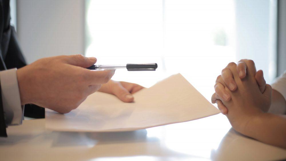 Seseorang yang sedang memberikan pulpen dan kertas dokumen sebagai ilustrasi dari pendanaan jangka pendek.