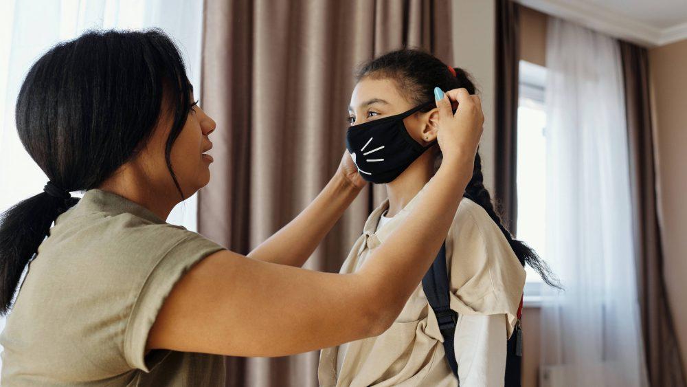 Seorang ibu yang sedang memakaikan masker kain kepada putrinya.