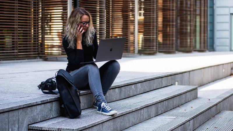 Seorang wanita yang sedang duduk di tangga sambil menggunakan ponsel dan laptopnya.