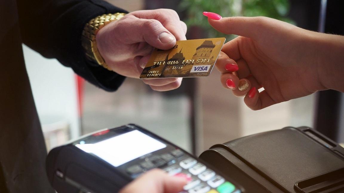 Seseorang sedang melakukan transaksi menggunakan kartu atm.