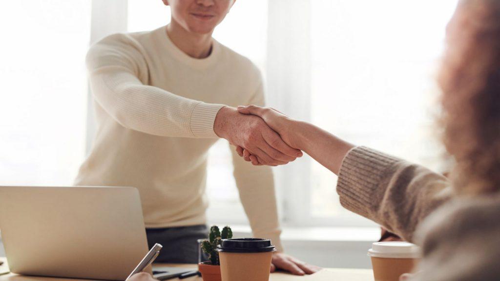 Ilustrasi surat hibah, dua orang berjabat tangan