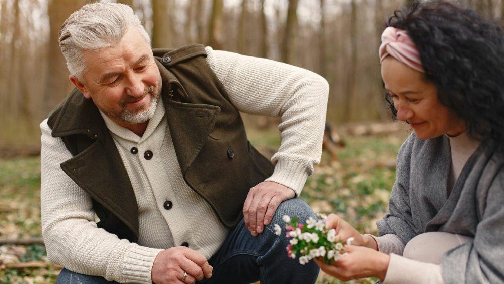 Seorang pria dan wanita yang sedang memetik bunga.