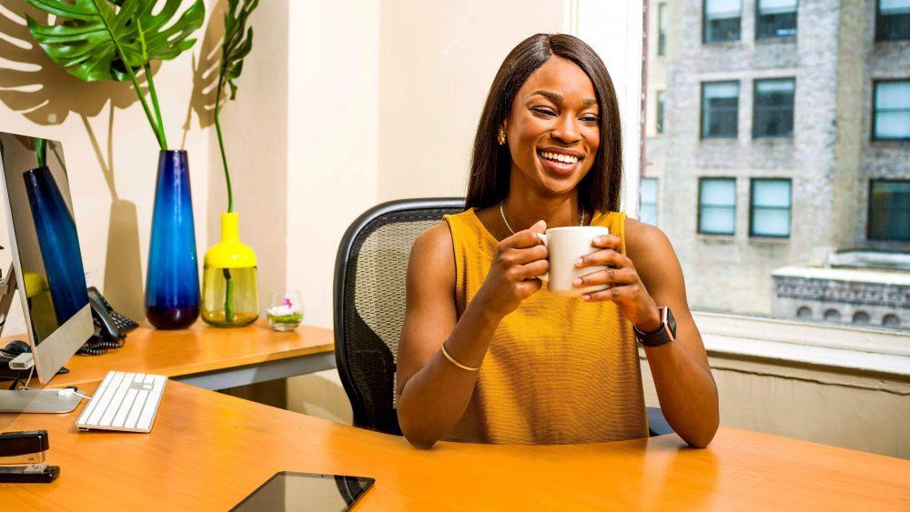 Seorang perempuan yang sedang tersenyum sambil memegang sebuah cangkir.