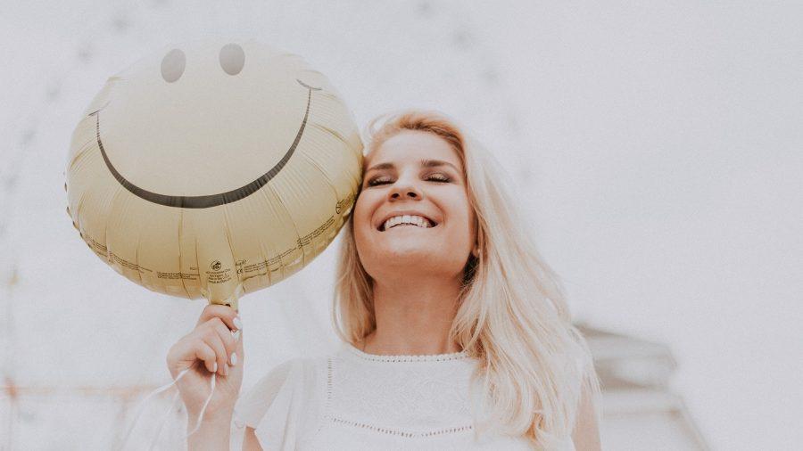 Seorang wanita yang sedang tersenyum memegang balon.