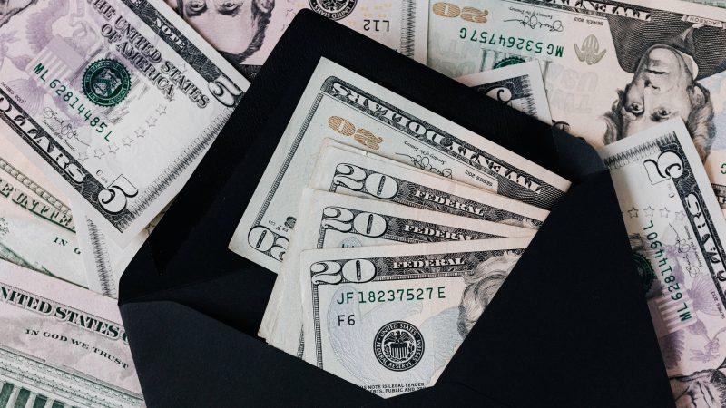 Uang yang diletakkan di dalam amplop berwarna hitam.