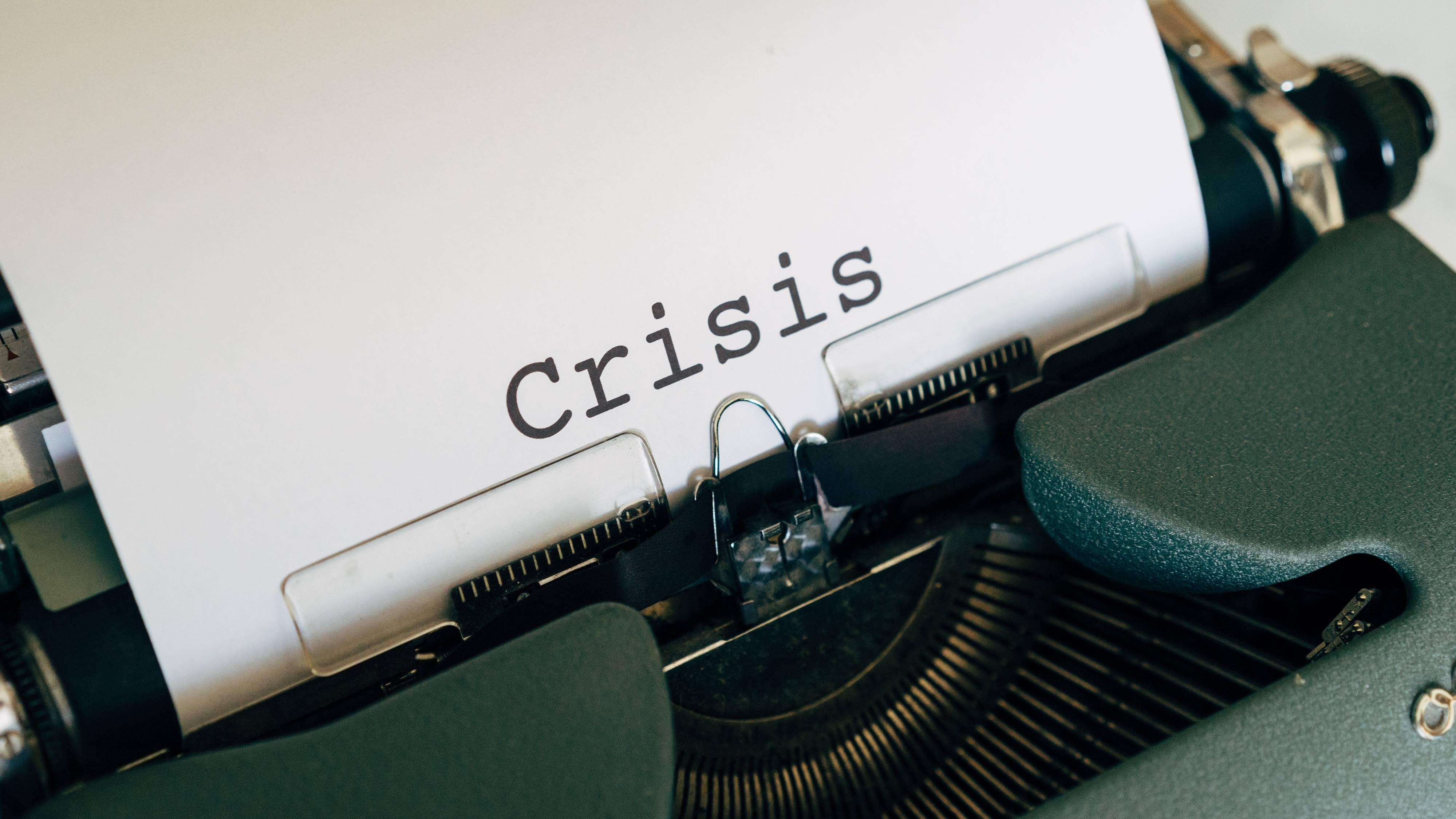 """Kertas yang bertuliskan """"crisis"""" diketik dengan mesin ketik."""