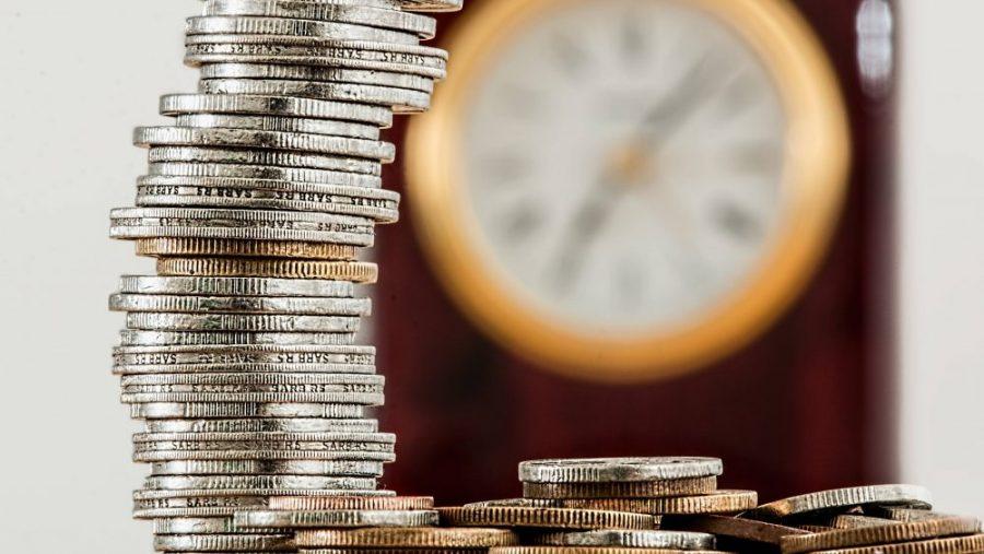 Uang dan jam yang menggambarkan investasi reksa dana.