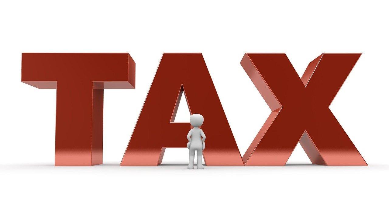 """Ilustrasi seseorang yang sedang berdiri di depan tulisan """"tax""""."""