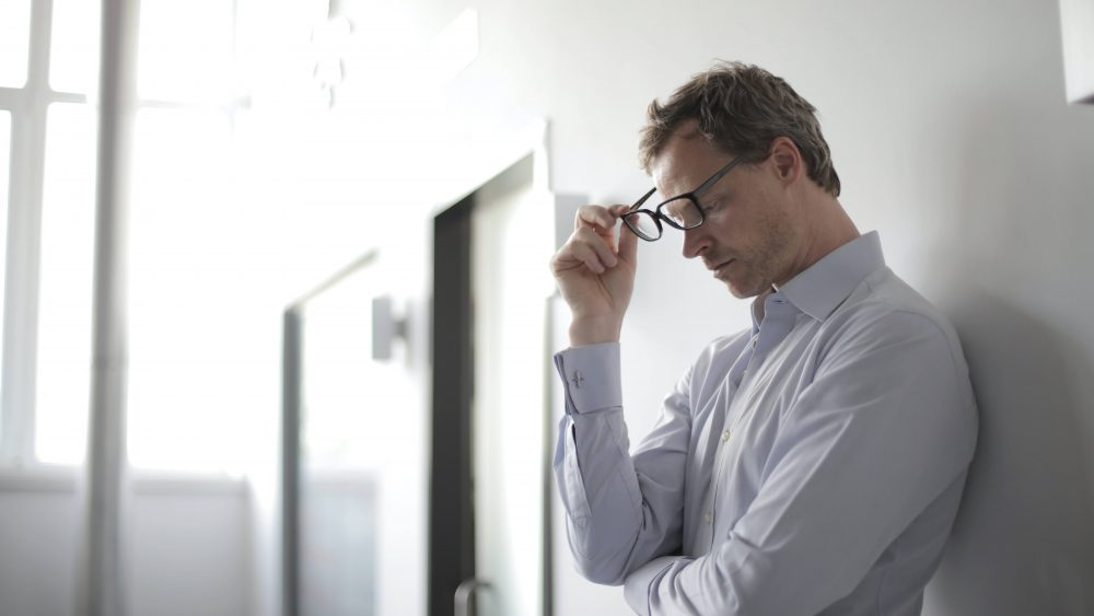 Seorang pria yang sedang termenung sembari memegang kacamata.