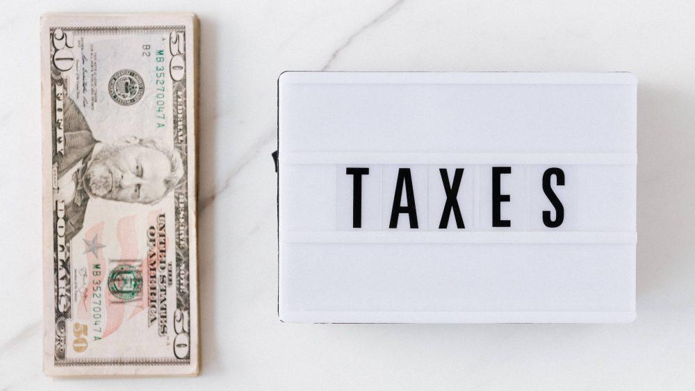 """Uang dolar dan tulisan '""""Taxes""""."""
