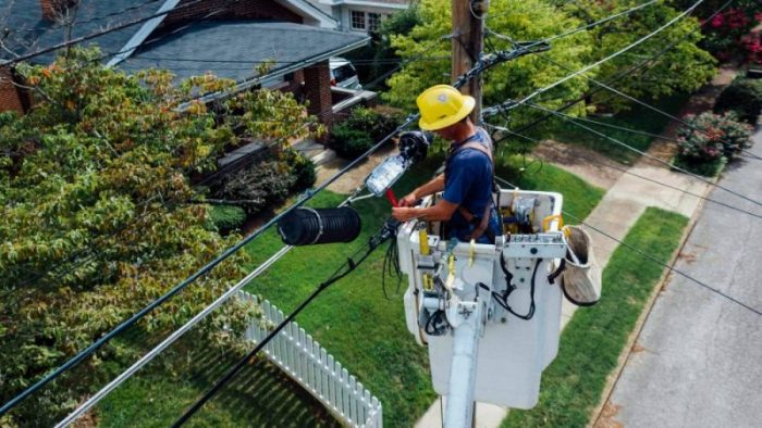 Seorang petugas listrik yang sedang menambah daya listrik.