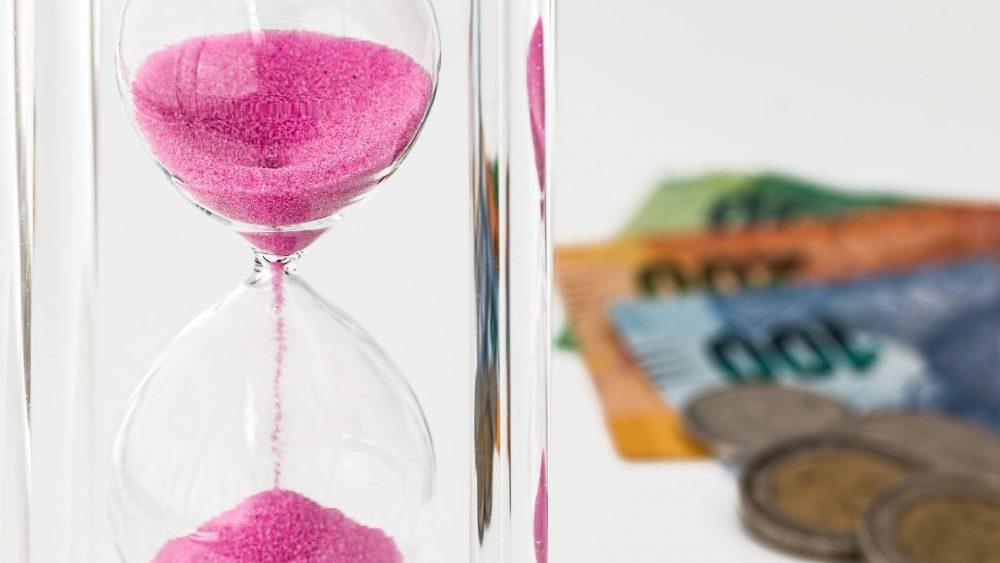 Sebuah jam pasir dan sejumlah uang yang menggambarkan ilustrasi deposito.