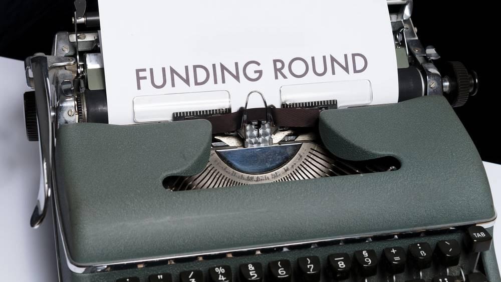 """Mesin tik dengan kertas bertuliskan """"Funding Round""""."""