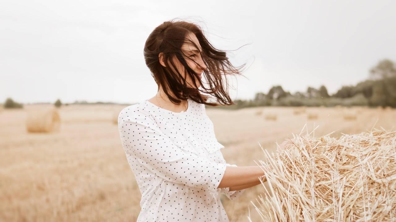 Seorang wanita yang sedang tersenyum dengan rambut yang berterbangan terbawa angin.
