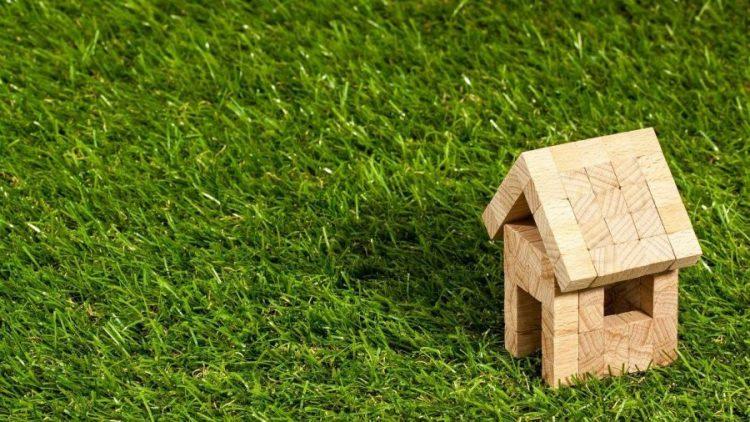 Rumah kayu kecil yang berada di atas rumput.