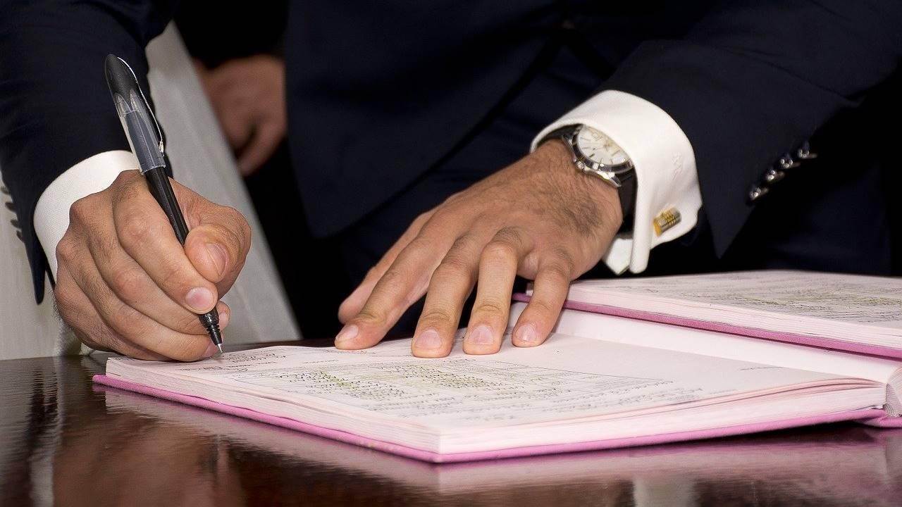 Ilustrasi seseorang sedang menandatangani surat tanah.