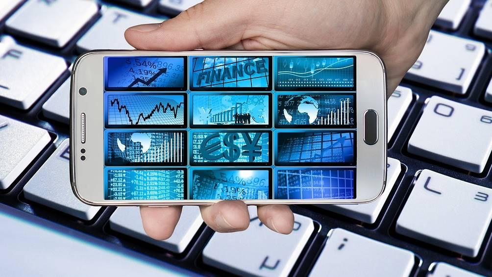 Seseorang sedang memegang ponsel dengan layar yang menunjukkan ilustrasi komoditi.