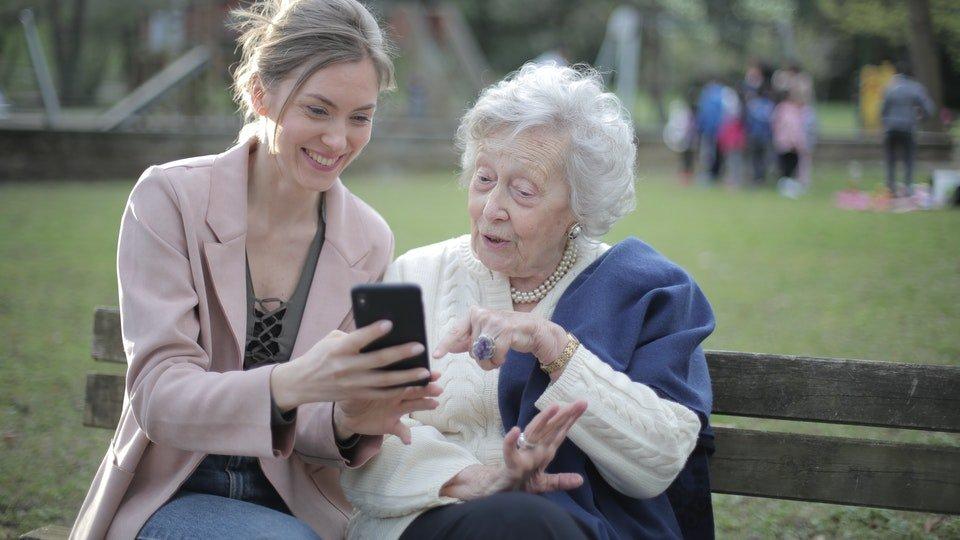 Seorang wanita yangs edang menunjukkan ponselnya ke wanita paruh baya.