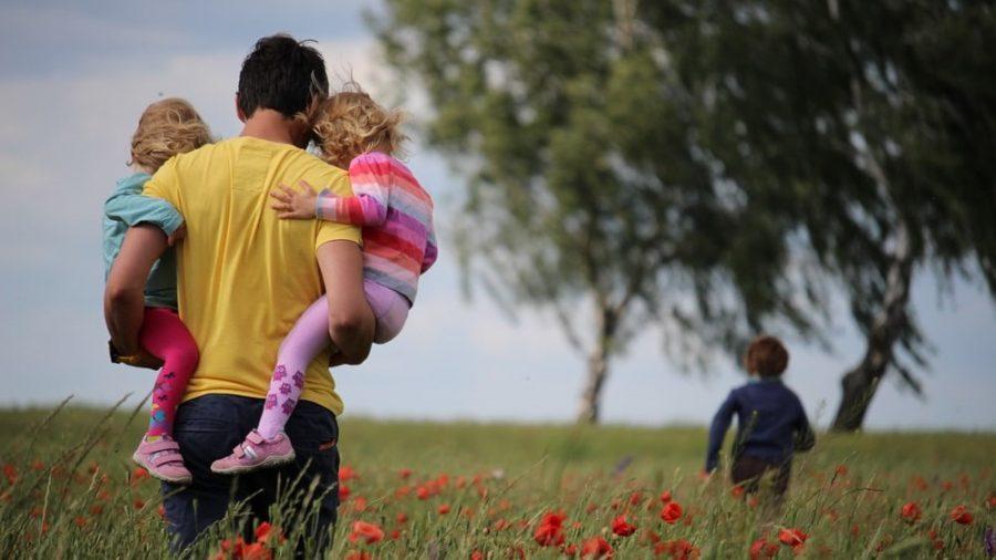 Seorang ayah yang sedang menggendong kedua anaknya.