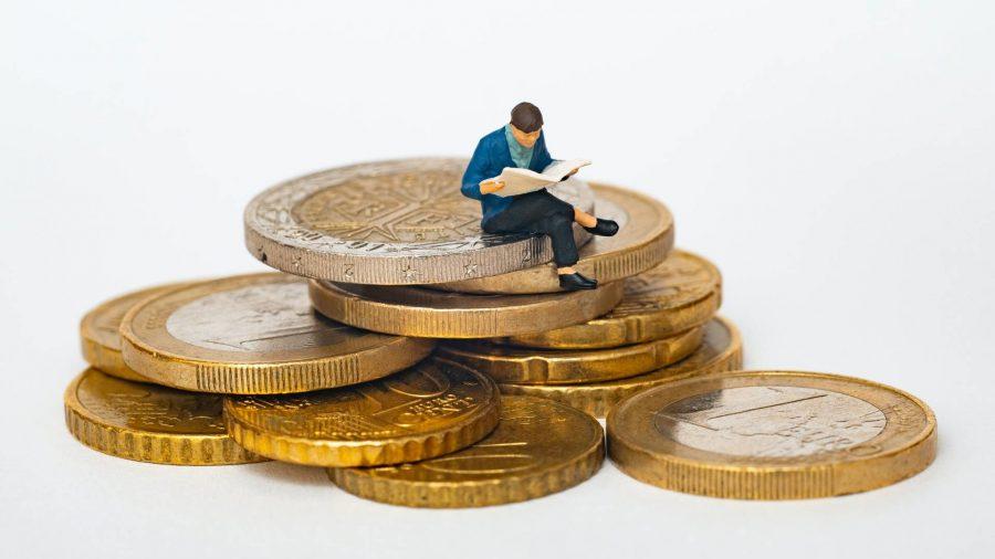 Miniatur pria yang sedang duduk di atas koin.