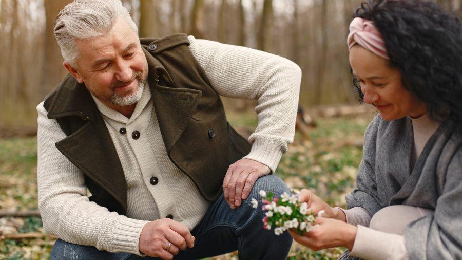 Kakek dan nenek yang sedang melihat bunga.