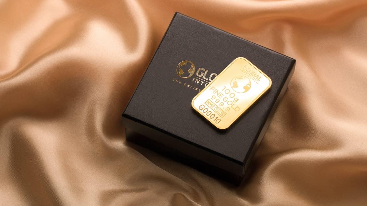 Logam mulia emas di atas kotak hitam.