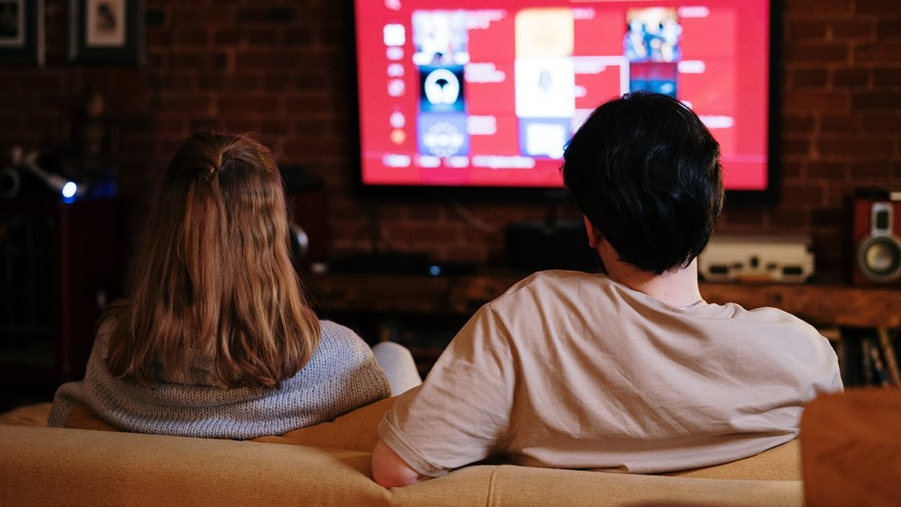 Ilustrasi dua orang yang sedang melihat iklan tv.