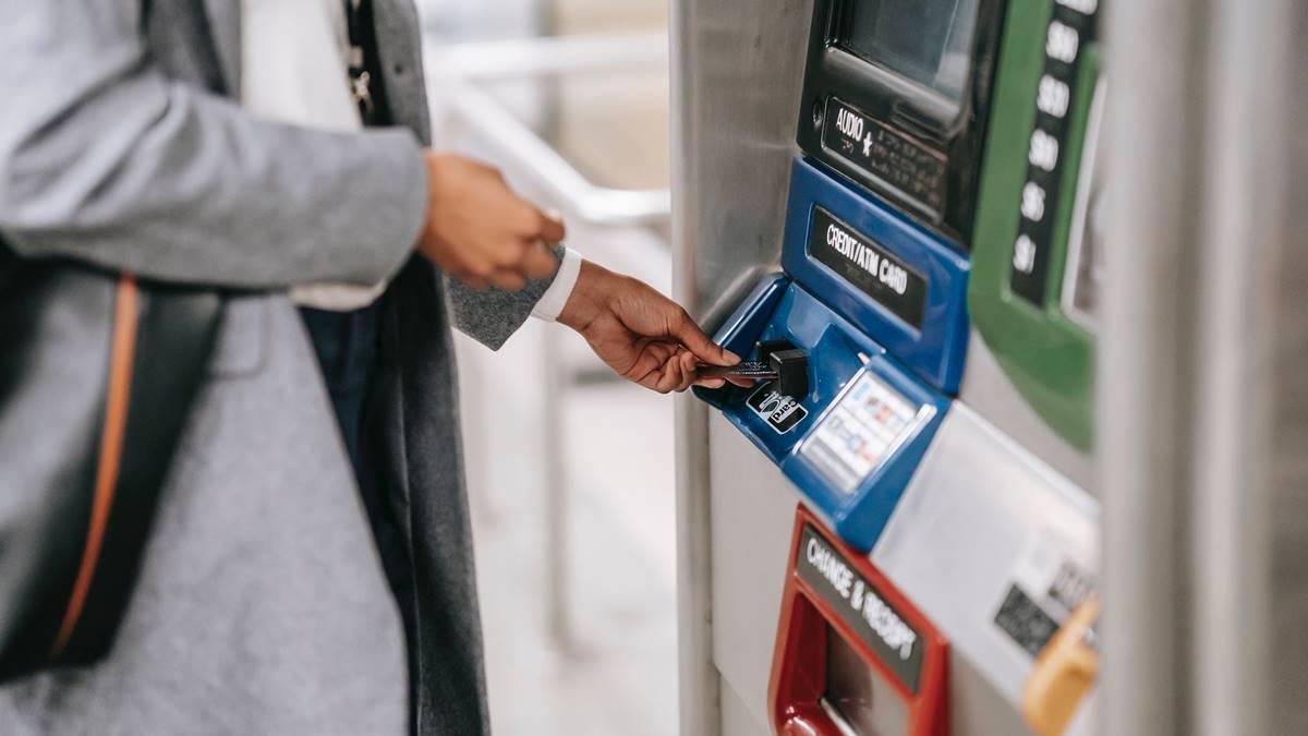 Seseorang yang sedang ingin melakukan transfer antar bank melalui mesin ATM.