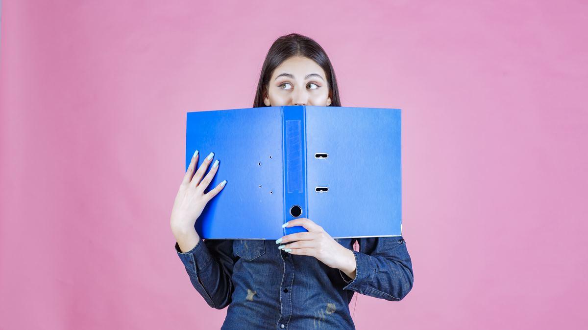 Seorang wanita yang introvert menutupi wajahnya dengan sebuah file.