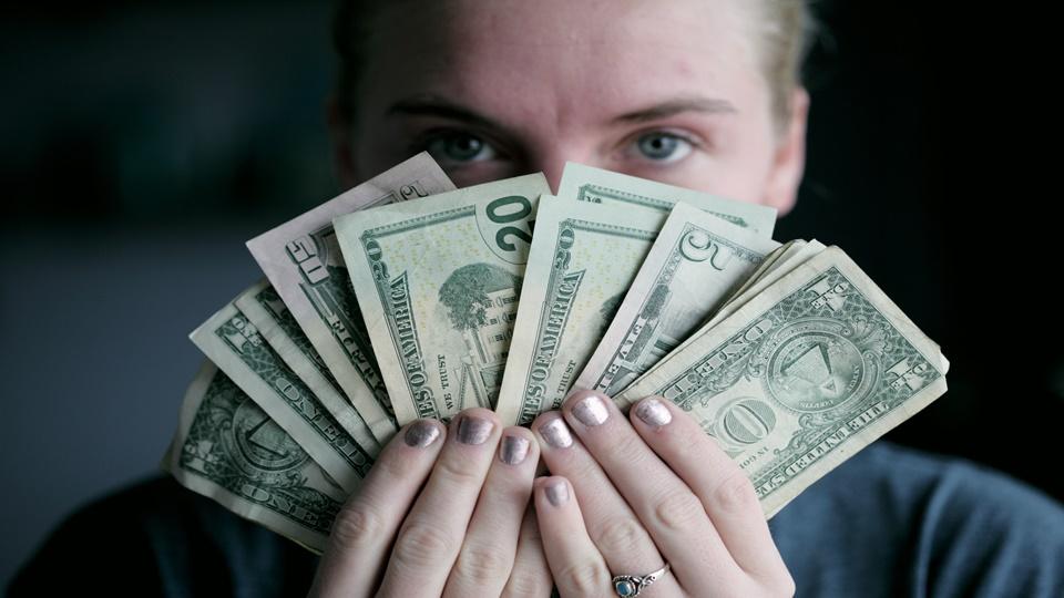 Seorang pria yang sedang memegang sejumlah uang bonus kerja.