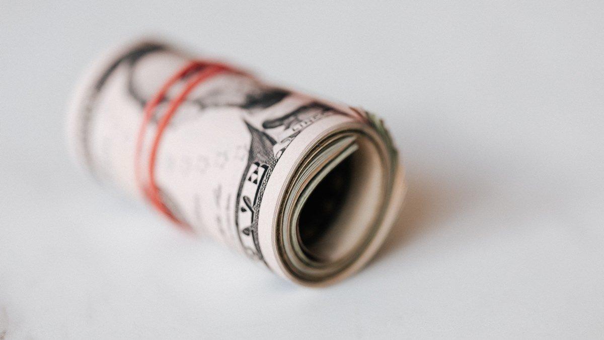 Sejumlah uang yang digulung dan diikat menggunakan karet.