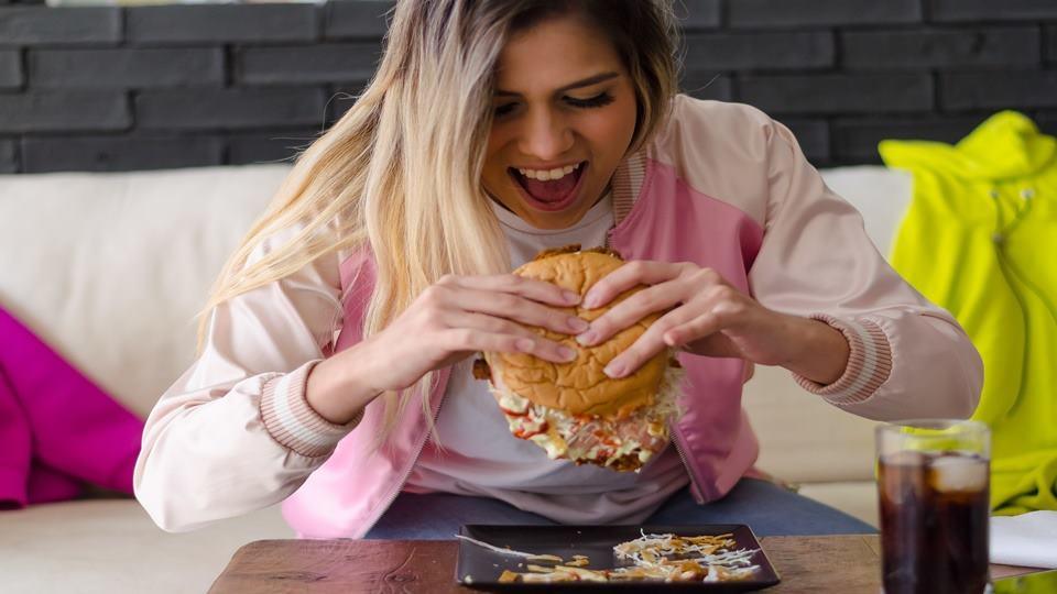 Seorang wanita yang sedang memakan burger.